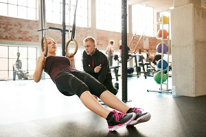 Personal trainer helping woman on he