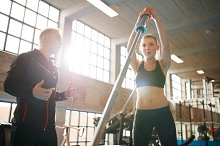 Woman exercising with trainer at fit