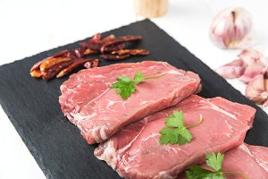 Raw beef steak with peppers and herb