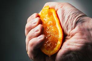 man dramatic squeezes orange.