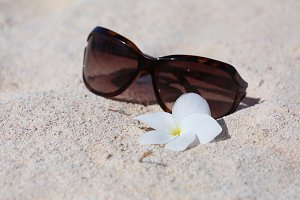 Sunglasses on a sand with white flow