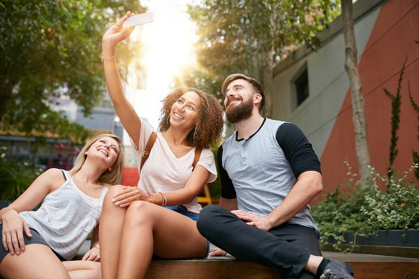 Smiling friends taking selfie with…