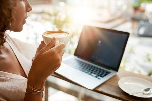 Woman drinking coffee with a laptop