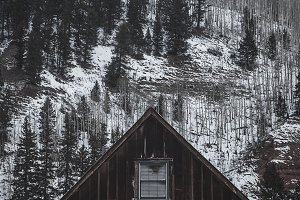 Cabin in Front of a Snowy Mountain