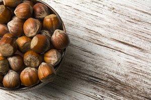hazelnuts in wooden bowl on rustic b
