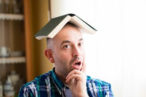 man with a book on his head.