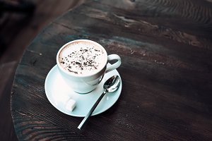 Cup of cappuccino on old dark table