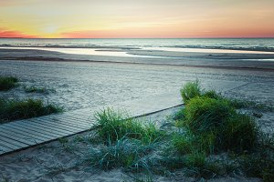 Wooden footpath to the sea at sunset