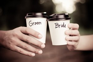Groom and bride holding coffee cup