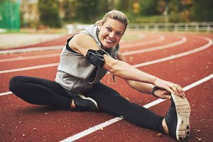 Smiling woman stretching after run