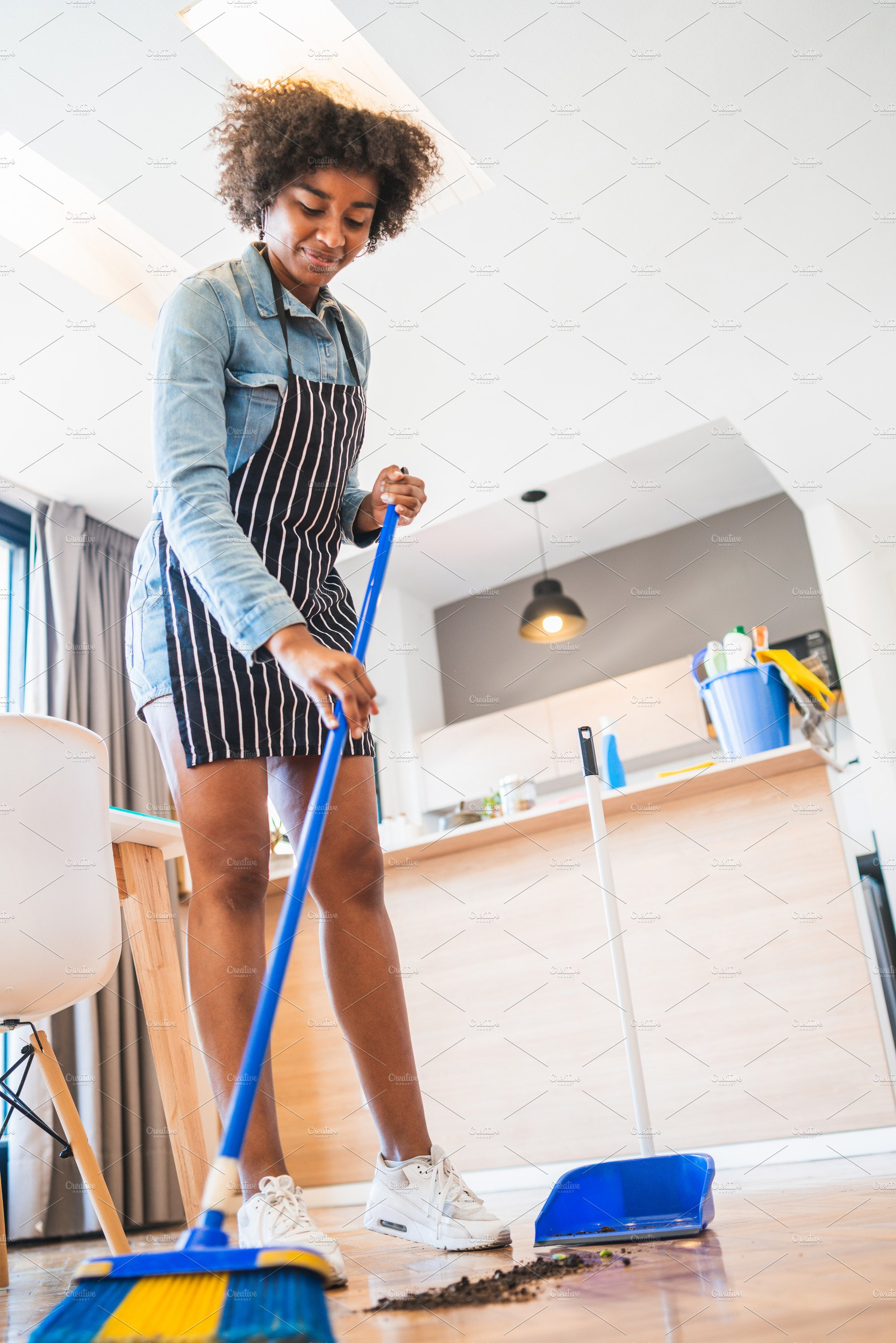 afro woman sweeping floor with broom high quality stock photos creative market creative market