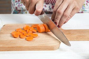 Woman cutting vegetables on wooden b