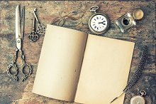 Open book and vintage writing tools
