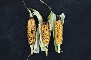 Grilled corn over black slate stone