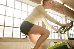 Fitness woman on bicycle in gym