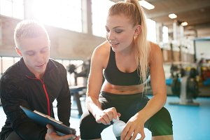 Personal trainer helping young woman