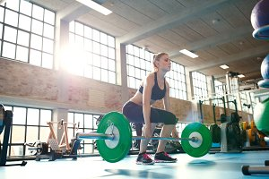 Female athlete lifting weights in he