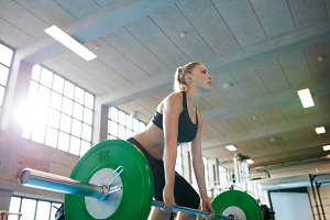 Young female weightlifter focusing b