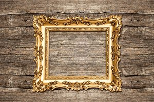 Golden frame on wooden background