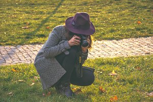 A woman in a hat taking photos