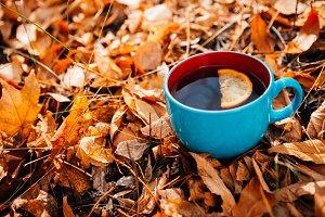 blue cup of coffee  or tea on leaves