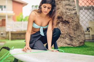 Woman with wetsuit waxing surfboard