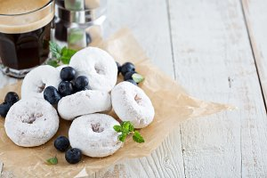 Powdered sugar donuts on parchment