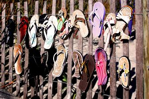 Flip flops on a wood fence