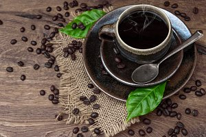 Black coffee with beans and leaves