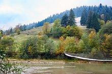 Mountain river with hanging bridge