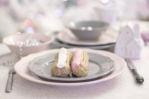 French confectionery, pink and white Eclair on gray dish
