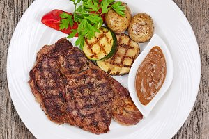 Grilled steaks, baked potatoes and v