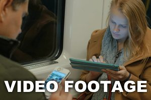 Woman in Metro Train Typing Tablet