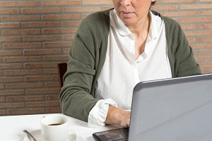 Woman at laptop with coffee cup