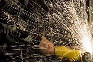 Guy drills metal grinder with sparks
