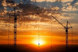 Hoisting cranes on sunset background