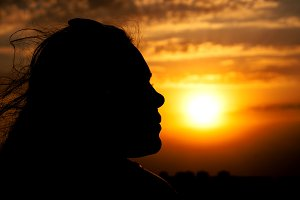 Young girl face silhouette on sunset