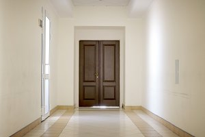 White hallway with brown door