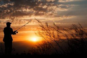 Fisherman on gold sunset background