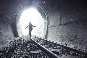 Child walking in railway tunnel.