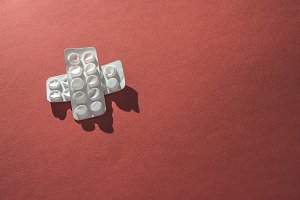 Packs of pills on red background