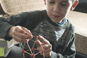 Child make house with wooden stick