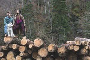 Young woman and men on wood logs in