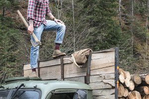 Young man on vintage truck with logs