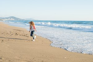 Young woman walking along beach