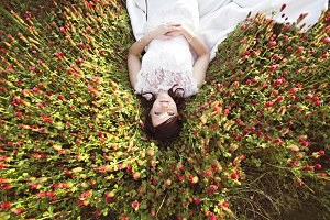 Bride Lying in a Field of Flowers
