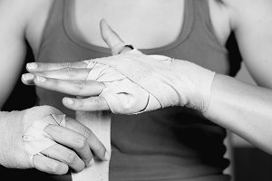 Female boxer tying up hands