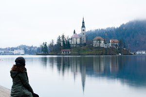 Girl sitting by lake Bled