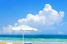 Beach chair and white umbrella on sa