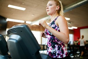 Fit woman running on treadmill in gy